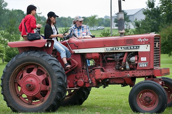 Tam Le, at left, and Mai Vu, center, both from Vietnam, take turns learning to drive a tractor following the tutelage of Cindy Martinell.